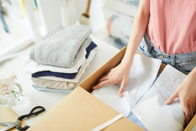 Woman packing clothes in box